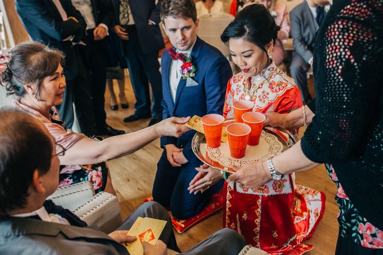 Chinese Tea ceremony with bride in red Chinese wedding dress and groom in tuxedo