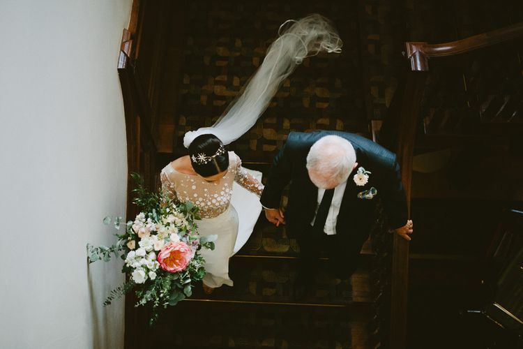 Bride in Applique Rime Arodaky Long Sleeve Wedding Dress Walking Down the Stairs at Cowley Manor