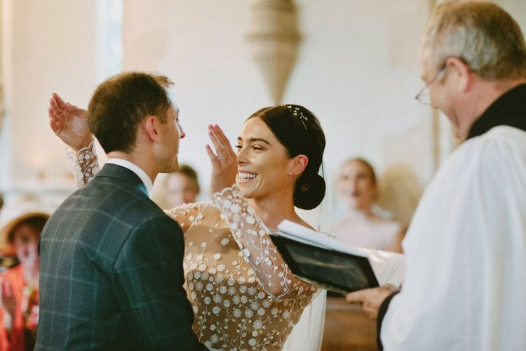 Wedding Ceremony with Bride Laughing in Applique Rime Arodaky Long Sleeve Wedding Dress and Groom in Checked Suit