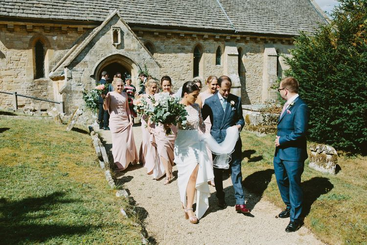 Bride in Rime Arodaky  Applique Long Sleeve Wedding Dress and Groom in Checked Suit Being Followed By the Bridal Party