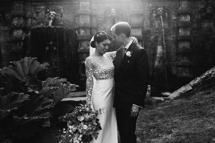 Bride in Applique Rime Arodaky Long Sleeve Wedding Dress and Groom in Dark Suit Embracing