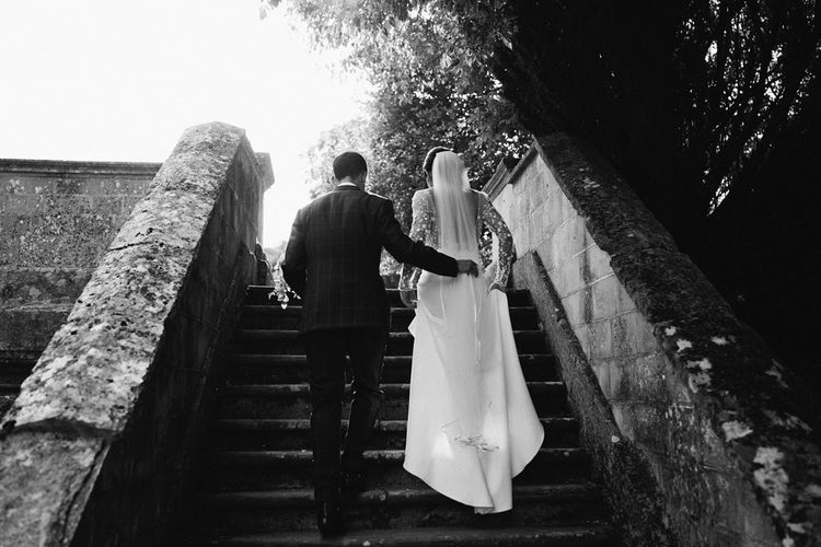 Groom Holding his Brides Train as She Walks Up Steps