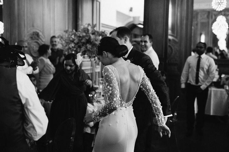 Bride in Applique Rime Arodaky Long Sleeve Wedding Dress and Groom in Dark Suit Entering the Wedding Reception