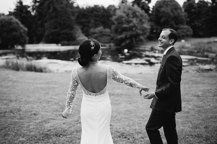 Bride in Applique Rime Arodaky Long Sleeve Wedding Dress and Groom in Dark Suit Holding Hands