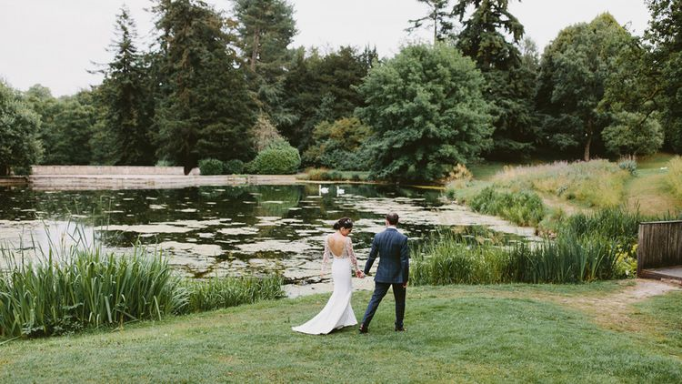 Bride in Applique Rime Arodaky Long Sleeve Wedding Dress and Groom in Dark Suit in Coley Manor Gardens