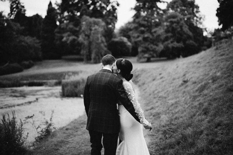 Bride in Applique Rime Arodaky Long Sleeve Wedding Dress Kissing her  Grooms Cheek