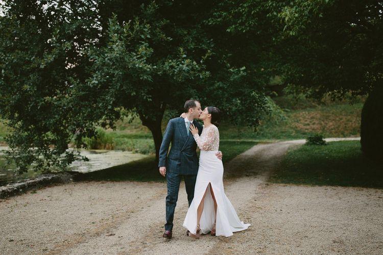 Bride in Applique Rime Arodaky Long Sleeve Wedding Dress and Groom in Dark Suit Kissing