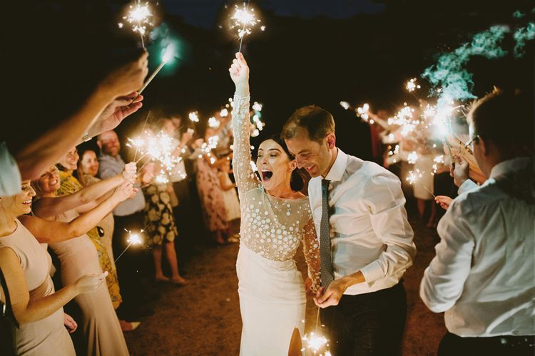 Sparkler Moment  with Bride in Applique Rime Arodaky Long Sleeve Wedding Dress and Groom in Shirt & Tie