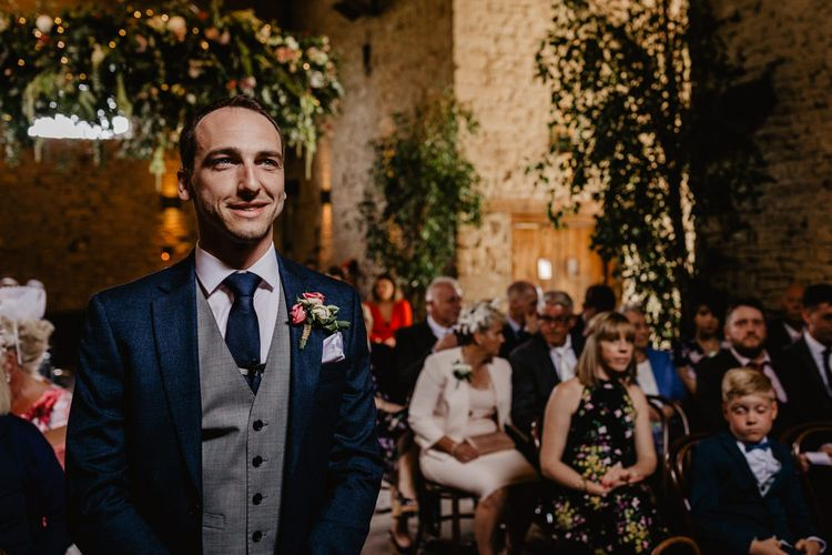 Groom Standing at the Altar  in a Navy Suit with Grey Waistcoat