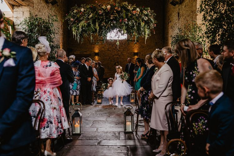 Flower Girls in Tulle Tutu Walking Down the Aisle with a Greenery Chandelier