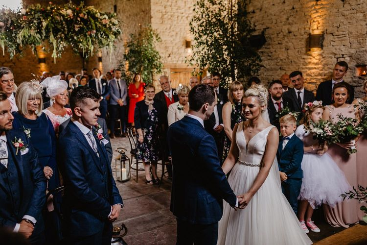 Bride in Stella York Wedding Dress with Tulle Skirt and Groom in Navy Suit Exchanging Vows at Cripps Barn Altar