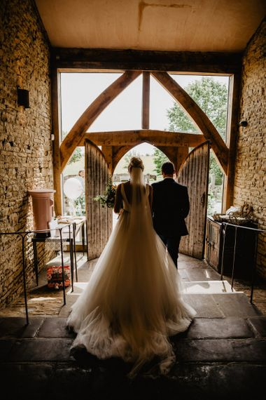 Bride in Stella York Wedding Dress and Cathedral Length Veil and Groom in Navy Suit Standing at the Entrance to Cripps Barn