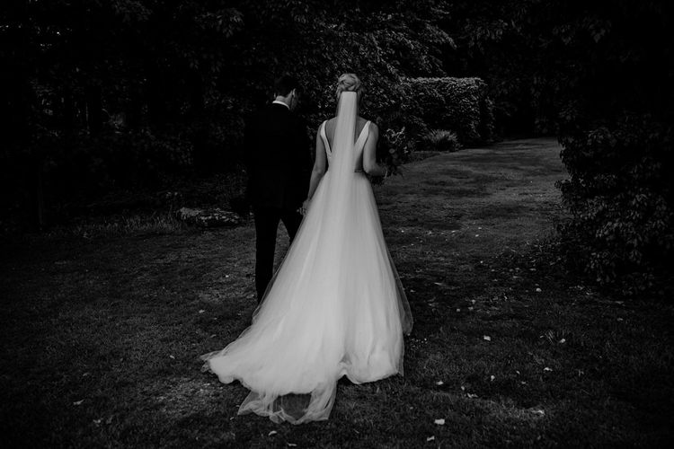 Bride in Stella York Wedding Dress and Cathedral Length Veil and Groom in Navy Suit  Walking Hand in Hand
