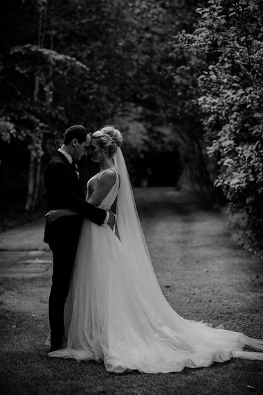 Bride in Stella York Wedding Dress and Cathedral Length Veil and Groom in Navy Suit Embracing