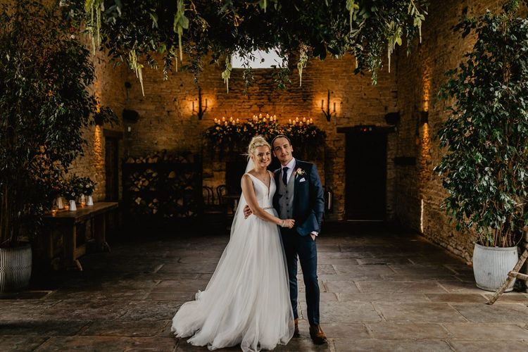 Bride in Stella York Wedding Dress with Tulle Skirt and Groom in Navy Wedding Suit