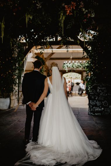 Bride in Stella York Wedding Dress with Cathedral Length Veil and Groom in Navy Wedding Suit Waiting to Enter The Wedding Breakfast