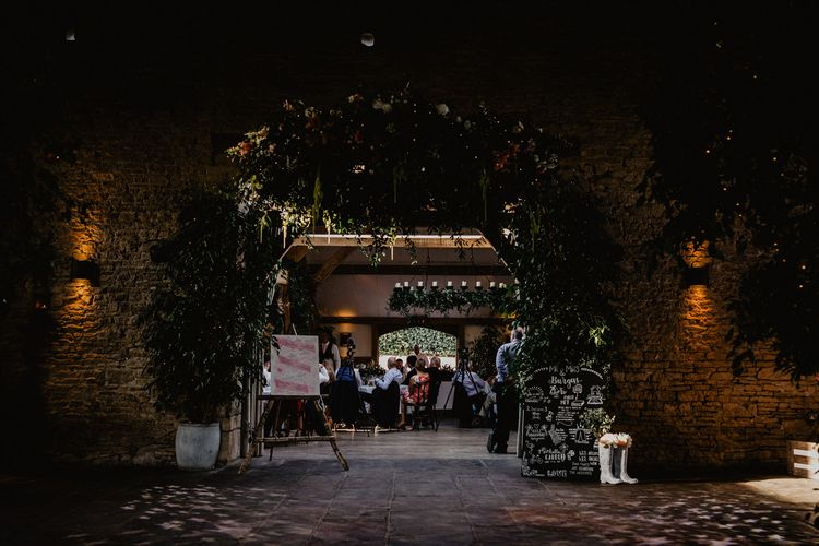 Cripps Barn Wedding Reception Decor with Floral Chandelier, Chalkboard Sign and Wellington Boots