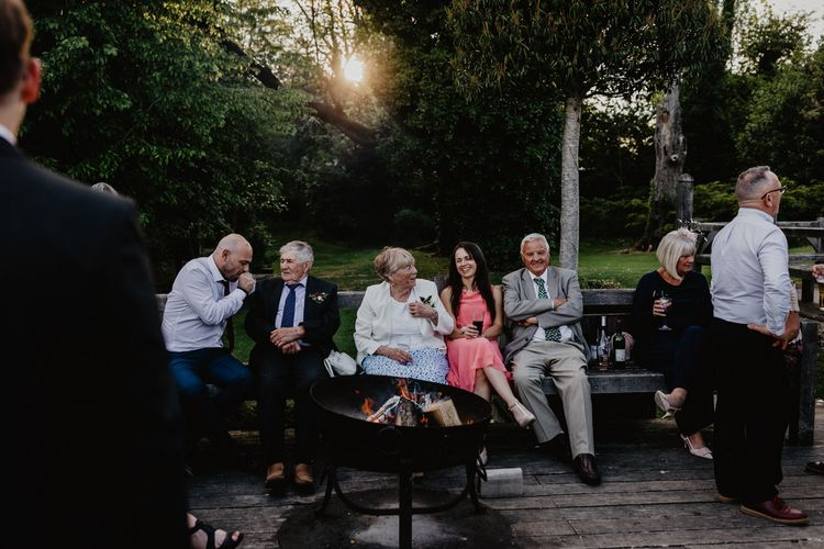 Wedding Guests Sitting Around the Outdoor Firepit