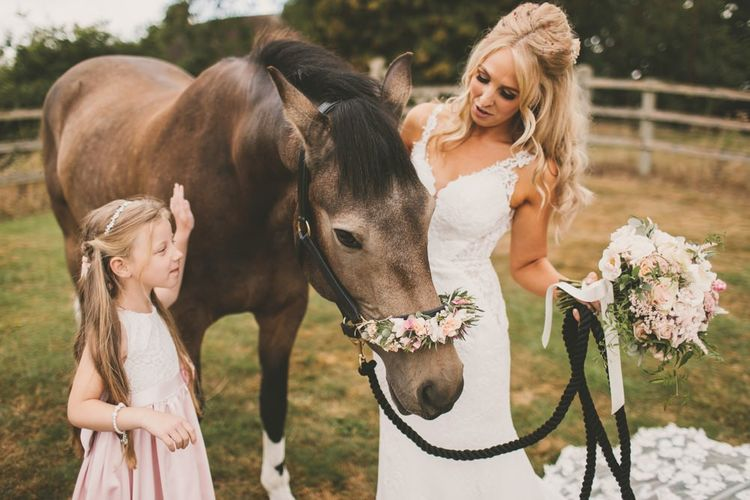 Bride with horse at wedding and blush bouquet