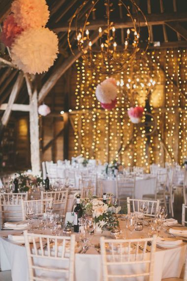 Pink pom pom decorations with fairy light backdrop