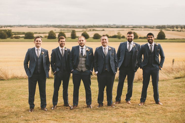 Groomsmen in navy suits with bridal party in pale blue bridesmaid dresses