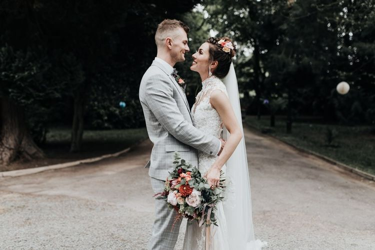 Bride and Groom Embrace with Bright Flowers and Veil