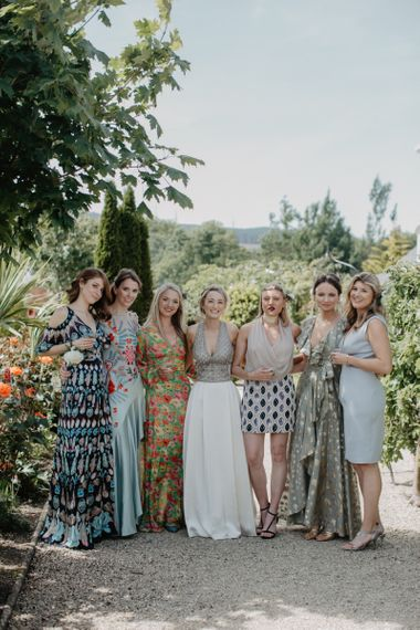Bride in Embellished Gold Halterneck Top and Satin Skirt with Wedding Guests in Pretty Dresses