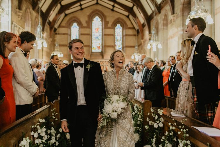 Bride and Groom Walk Back Down Aisle Laughing With Guests