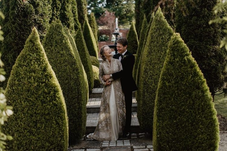 Bride And Groom Embrace In House Gardens