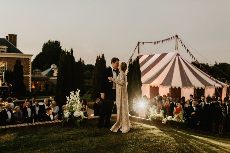 Bride and Groom Kiss In front Of Marquee Reception