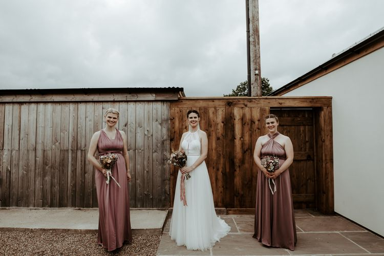 Bride and bridesmaids in dusky pink dresses at socially distanced Eden Barn wedding