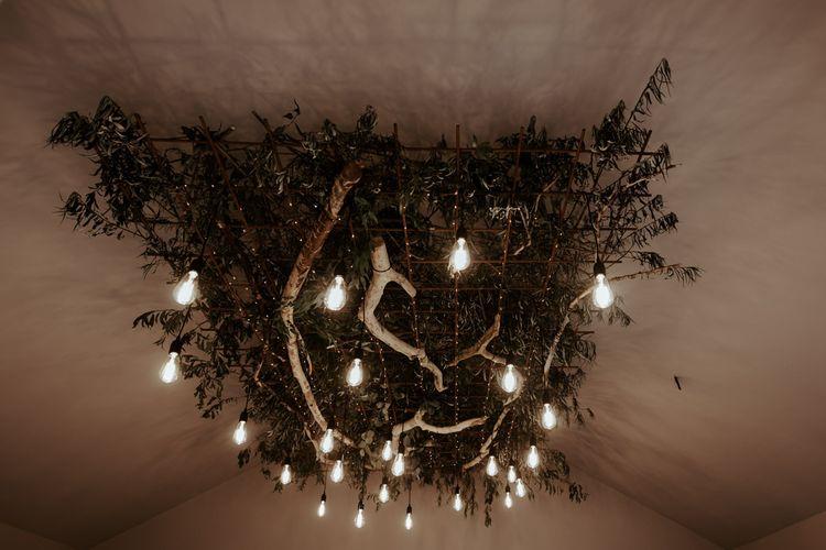 Wedding decor with festoon lights, foliage and drift wood