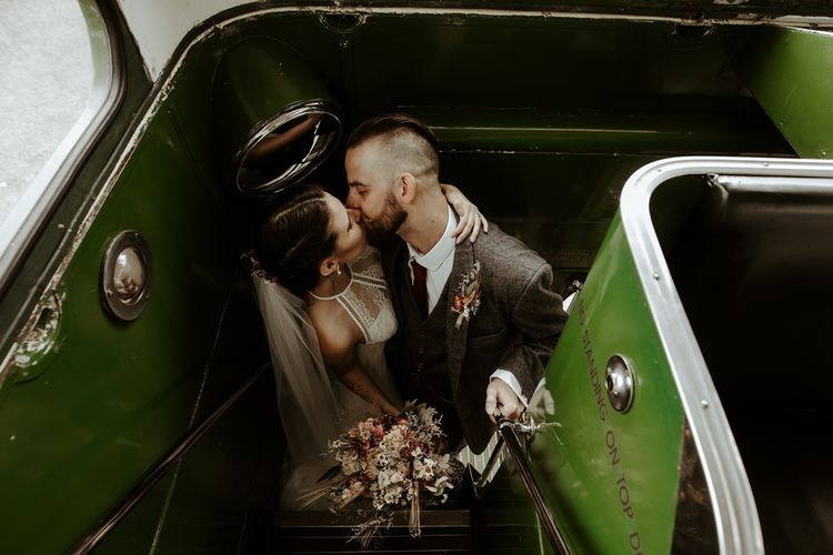 Bride and groom kissing on the vintage bus
