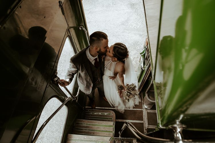 Bride and groom kissing on a vintage wedding bus