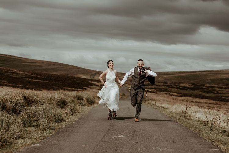 Bride and groom running in the Lake District at Eden Barn wedding