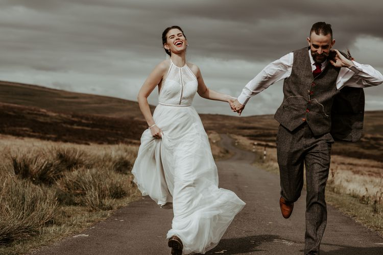 Bride in Willowby Watters wedding dress and groom in wool suit running along the country lane