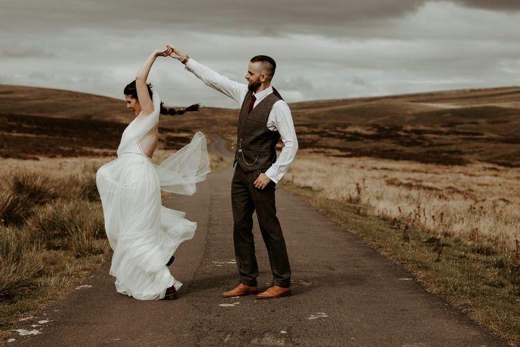 Groom in wool suit twirling his bride in Willowby Watters wedding dress