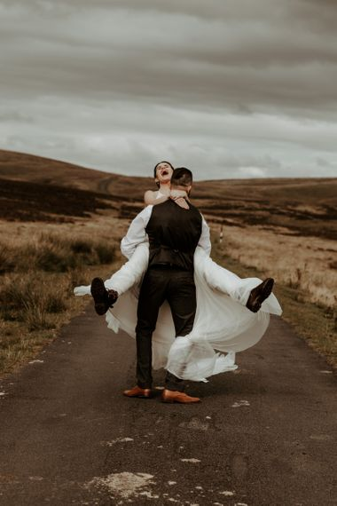 Groom picking up his bride in Willowby Watters wedding dress and boots