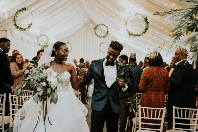 Bride and groom at marquee ceremony with wooden wedding signs and hoop decor