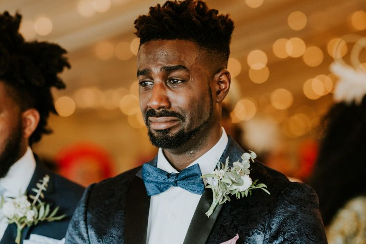 Groom in blue bowtie gets emotional during wedding ceremony