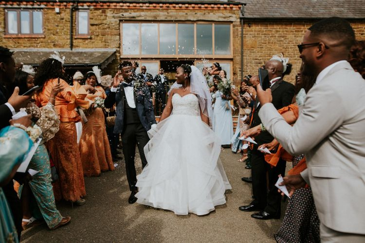 Confetti exit for bride in strapless wedding dress and groom in blue dinner jacket