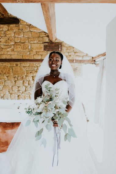 Bride with large bouquet and strapless wedding dress