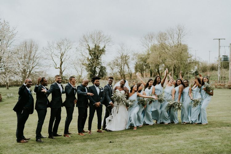 Bridal party in blue bridesmaid dresses with groomsmen