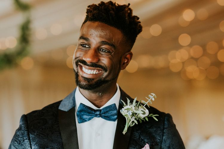 Groom in blue bowtie and dinner jacket