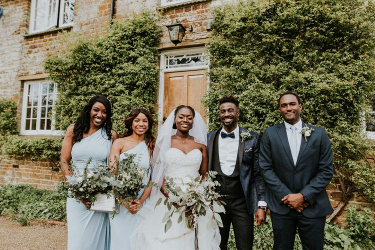Bride and groom with bridesmaids in blue dresses