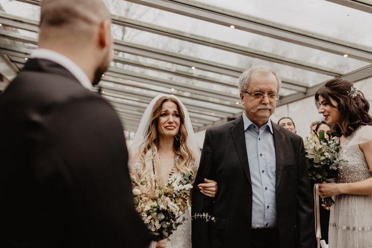 Bride walks up aisle to meet groom in brown wedding suit