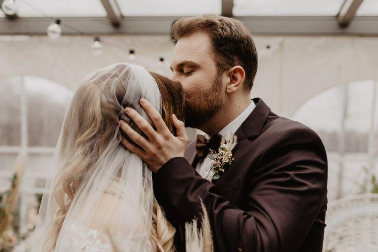 Bride in long veil greets groom in brown wedding suit