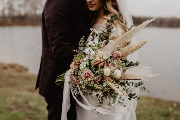 Groom in brown wedding suit with bride holding dried bouquet