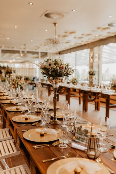 Tall flower centrepieces on long banquet tables for boho wedding