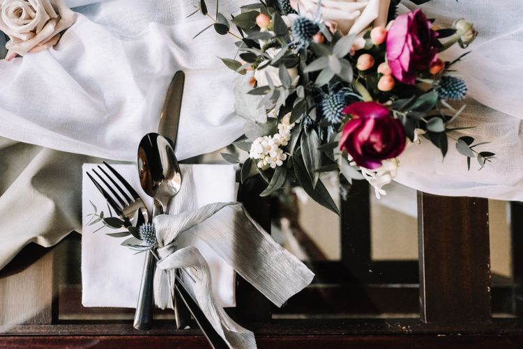 Cutlery tied with silk chiffon and wedding flowers